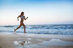 Sporty woman run at sea cost Stock Images