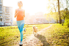 Sporty woman runing with dog Stock Photo