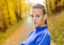 Sporty woman runner listens to music in nature Stock Images