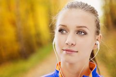 Sporty woman runner listens to music in nature Stock Photo