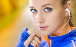 Sporty woman runner listens to music in nature Stock Image