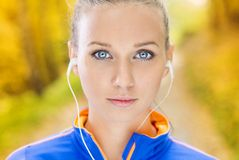 Sporty woman runner listens to music in nature Royalty Free Stock Photos