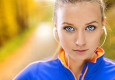 Sporty woman runner listens to music in nature Royalty Free Stock Images