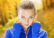 Sporty woman runner listens to music in nature Royalty Free Stock Image