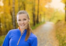 Sporty woman runner listens to music in nature Stock Photography