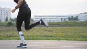 Sporty woman runner running on road at the stadium. Slow motion stock video