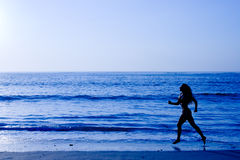 Sporty woman running along beach Stock Photos