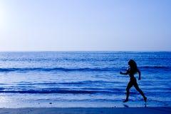 Sporty woman running along beach Stock Photos