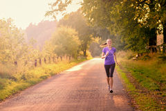 Sporty woman running on a country road Stock Photos