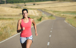 Sporty woman running in country road Royalty Free Stock Image