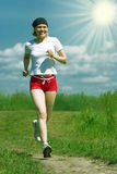Sporty woman running on field road Royalty Free Stock Photography