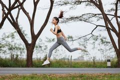 Sporty woman running and jumping in park. Sporty woman running and jumping in the park Royalty Free Stock Photography