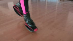 Sporty woman running in kangoo shoes in the gym. Close-up. The camera focuses on the legs of the woman in black trousers. Sporty woman slowly walking in gym. The stock video