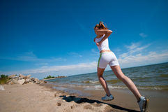 Sporty woman running in sea coast. Beautiful young sport woman running in sea coast on sunny summer day Royalty Free Stock Image