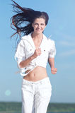 Sporty woman running in sea coast Royalty Free Stock Image