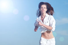 Sporty woman running in sea coast Stock Photos
