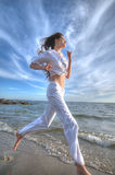 Sporty woman running in sea coast Stock Images