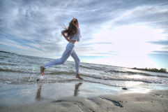 Sporty woman running in sea coast Royalty Free Stock Images