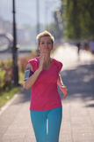 Sporty woman running  on sidewalk Stock Image