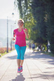 Sporty woman running  on sidewalk Royalty Free Stock Image