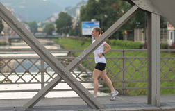 Sporty woman running  on sidewalk Stock Photos