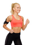 Sporty woman running with smartphone and earphones Stock Images
