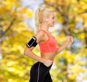 Sporty woman running with smartphone and earphones Royalty Free Stock Images