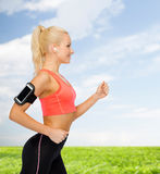 Sporty woman running with smartphone and earphones Stock Photography