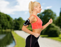 Sporty woman running with smartphone and earphones Royalty Free Stock Photos