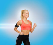 Sporty woman running with smartphone and earphones Stock Photo