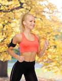 Sporty woman running with smartphone and earphones Stock Image