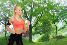 Sporty woman running with smartphone and earphones Royalty Free Stock Photo