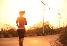 Sporty woman running sunrise Stock Image