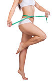 Sporty woman's body and measuring tape Royalty Free Stock Photos