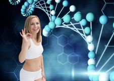 Sporty woman saying OK with the hand with dna chain and dark blue background. Digital composite of sporty woman saying OK with the hand with dna chain and dark royalty free stock image