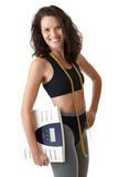 Sporty woman with scale. Happy sporty woman posing in sportswear with scale and tape measure Royalty Free Stock Image