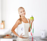 Sporty woman with scale, apple and measuring tape Royalty Free Stock Images