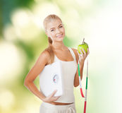 Sporty woman with scale, apple and measuring tape Stock Photography