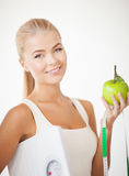 Sporty woman with scale, apple and measuring tape Royalty Free Stock Image