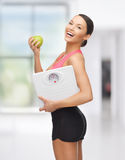 Sporty woman with scale and green apple Royalty Free Stock Images