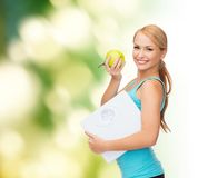 Sporty woman with scale and green apple Stock Photo