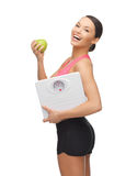 Sporty woman with scale and green apple stock photos