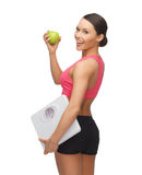 Sporty woman with scale and green apple Royalty Free Stock Photos