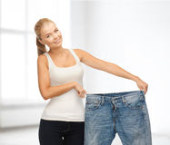 Sporty woman showing big pants Royalty Free Stock Images
