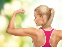 Sporty woman showing her biceps Royalty Free Stock Image