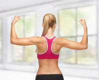 Sporty woman showing her biceps Royalty Free Stock Images
