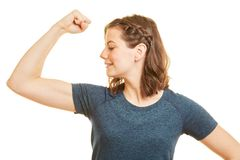 Sporty woman shows her arm muscles. As sign of strongness and power royalty free stock images