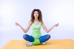 Sporty woman sititng in lotus pose on mat Stock Image