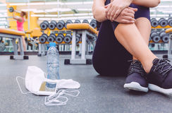 Sporty woman sitting with dumbbells, water and Royalty Free Stock Photos