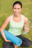 Sporty woman sitting with exercise mat and water bottle Royalty Free Stock Photos